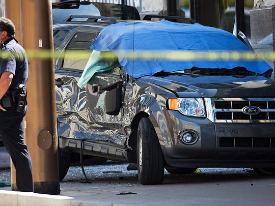 A Phoenix police officer stands near the Ford Escape