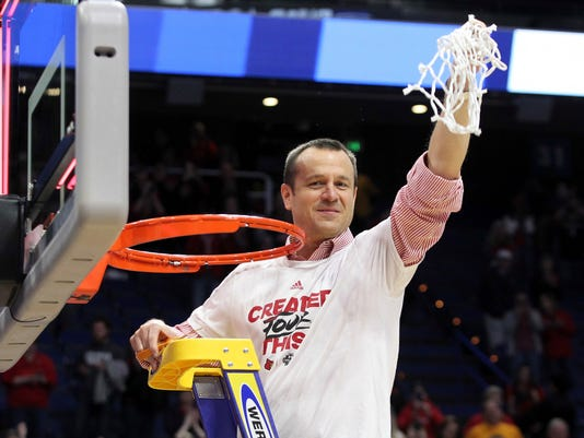 Louisville head coach Jeff Walz holds up the net after winning an NCAA women's college basketball tournament regional final over Oregon State 76-43, Sunday, March 25, 2018, in Lexington, Ky. (AP Photo/James Crisp)