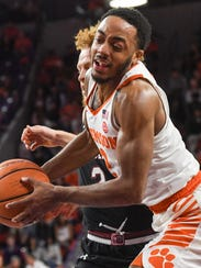 Clemson guard Marcquise Reed (2) gets bumped in the
