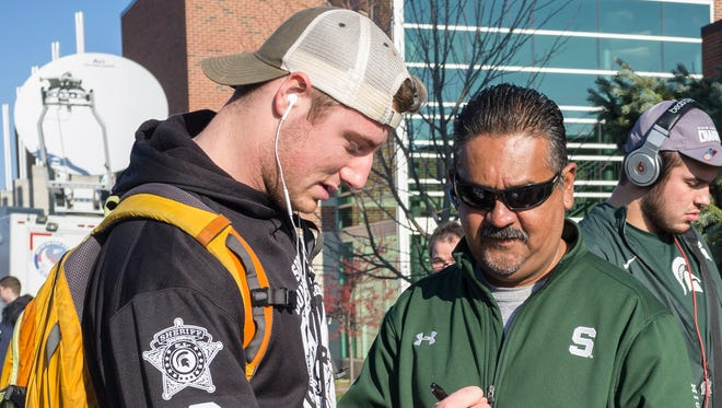 Michigan State football fan Alfredo Sifuentes, right, get a Connor Cook autograph as the Spartans arrive on campus Sunday, Dec. 6, 2015.