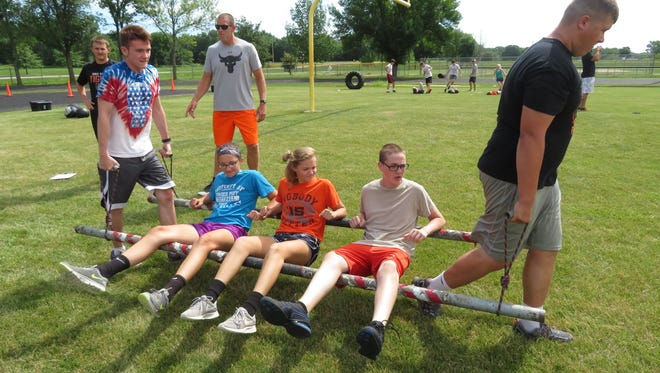 """Carrying athletes on a pole-constructed """"sled"""" were Joe Zuber (left) and Parker Wieck (right), while seated were (from second from left) Amelia Frimml, Jaden Smith and Tyler Bailey. Derek Leonard (left, back) and Jeremy Kriegel watch."""