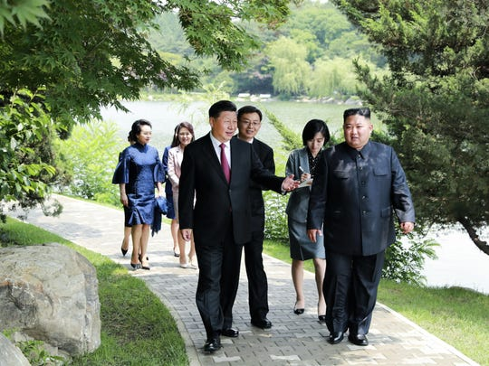 Chinese President Xi Jinping, left, and North Korean leader Kim Jong Un walk together at the state guest house in Pyongyang, North Korea.