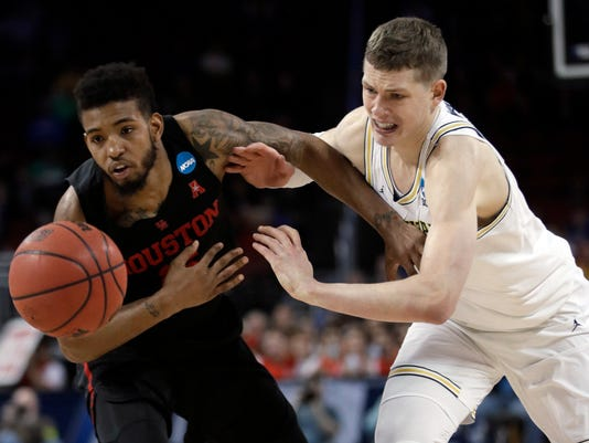 Houston forward Devin Davis, left, and Michigan forward Moritz Wagner chase the ball during the second half of an NCAA men's college basketball tournament second-round game, Saturday, March 17, 2018, in Wichita, Kan. Michigan defeated Houston 64-63. (AP Photo/Orlin Wagner)