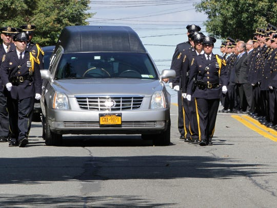 Polioce stand at attention as the hearse of Yonkers