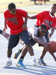 Mekhi Jones, 12, (center) can't squeeze between R.J. Toogood, 11, (left) and Jakobe McPhail, 11, as they play in the Pyramid Punch basketball league in Wilton Park.