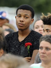 Keyshawn Wagner, 17, of Dearborn Heights, holds a flower, during the vigil. Mourners gathered to remember the victims, and some placed flowers and teddy bears throughout the day at the home where the four were killed.