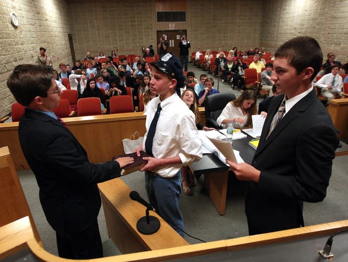 Philip Williams portraying Edward Snowden, l, is sworn in by bailiff David Calloway as defense attorney Nick Marini looks on as the 8th grade mock trial team from St. Rose Grammar School in Belmar takes on the controversial case of Edward Joseph Snowden in the Belmar Municipal Court, June 5, 2014, Belmar, NJ. Photo by Bob Karp
