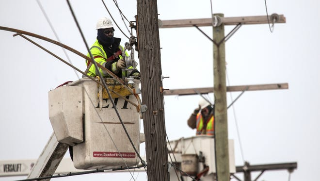 Lineman work on swapping out old streetlights as crews put up new LED streetlights along Conant in Detroit on Wednesday, March 4, 2015.