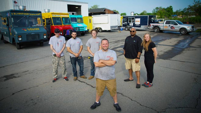 John Berl, owner of Custom Concessions, a food truck-building and repair business, stands with his fellow employees.