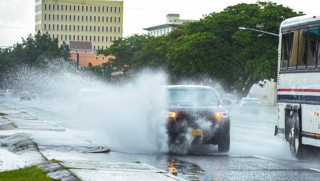 A motorist driving a Guam Community College vehicle splashes through water ponding on an outer lane as he attempts to overtake a bus on Marine Corps Drive in Hagåtña on Tuesday, July 3, 2018.