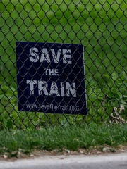 """A sign that reads, """"Save the Train"""" is placed inside"""