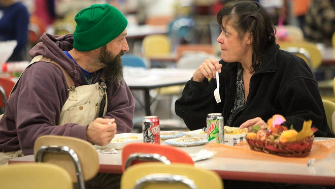 Mary Pena, right, talks with her friend Terry during a Thanksgiving feast held by Feed My Sheep Muncie Inc. The organization strove for food and fellowship by not only giving a warm meal and conversation, but also sending home bags of groceries to those in need.