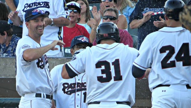 Somerset Patriots manager Brett Jodie congratulates his players during a game last season.