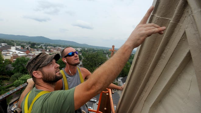 Chad Chambers, left, and Justin Krause, of Roger's Roofing, look at several spots on the St. Mary Church steeple in need of touch ups Wednesday. The two were on a lift about 140 feet in the air to finish painting and caulking the steeple in addition to pouring the cement corners the pinnacles will be attached to later this week.