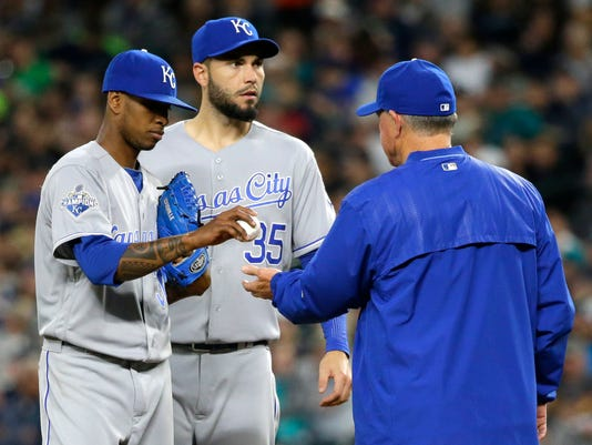 Kansas City Royals starting pitcher Yordano Ventura, left, is pulled during the fifth inning of the Royals' baseball game against the Seattle Mariners by manager Ned Yost, right, as first baseman Eric Hosmer, center, waits, Saturday, April 30, 2016, in Seattle. (AP Photo/Ted S. Warren)