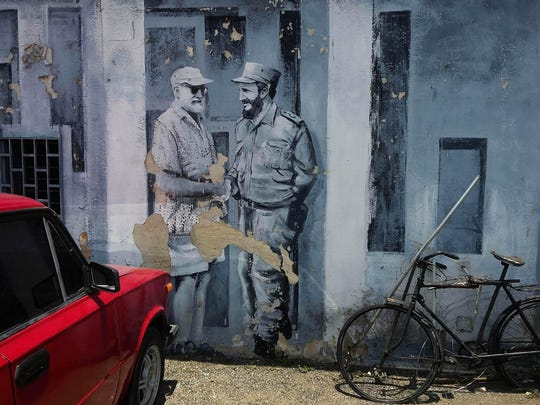 A mural of author Ernest Hemingway and Fidel Castro shaking hands covers a downtown parking lot in Havana, Cuba.
