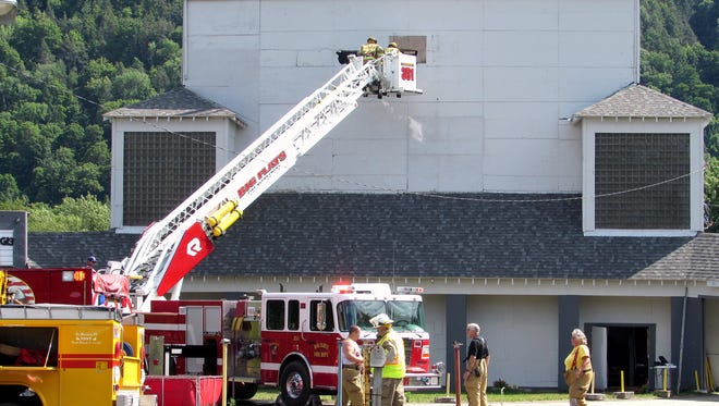 Firefighters break a hole in the back of the movie screen Friday at the Elmira Drive-In on state Route 352 in Big Flats.