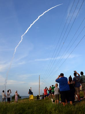 Spectators along SR 401 watch as a United Launch Alliance Delta IV lifts off from Cape Canaveral Air Force Station.