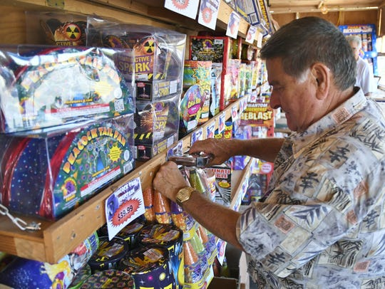 Members of Sequoia Triple X Fraternity get their firework booth on Akers Street and Goshen Avenue ready. The booth is one of many locations to buy safe and sane fireworks in Visalia.