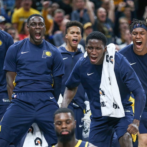 Players on the Indiana Pacers bench react to a...