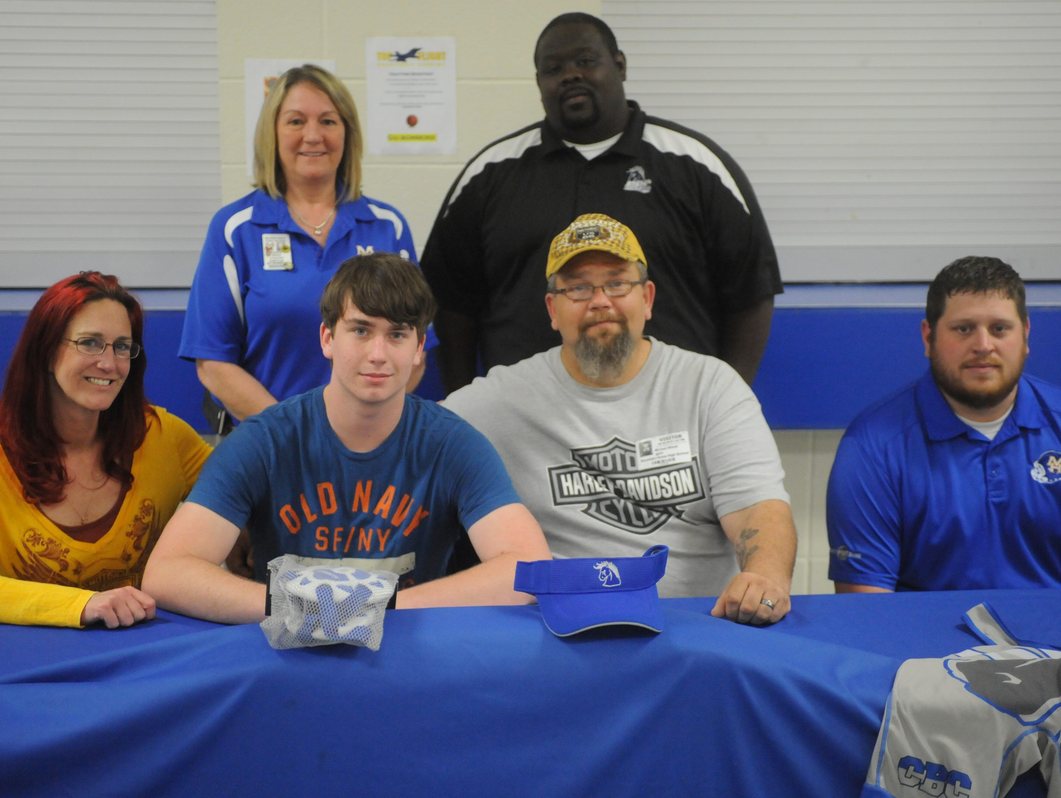 Mountain Home's Jesse Wheat, front row, second from left, signed a National Letter of Intent on Monday to wrestle at Central Baptist College in Conway. Shown with Wheat are: front row, from left, his mother, Cathy Wheat; his father, Mike Wheat; Mountain Home wrestling coach Damon Eikenhorst; back row, Mountain Home High School athletics director Janet Wood and CBC wrestling coach Ken Prophete.