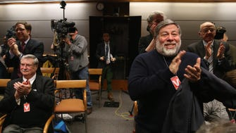 Apple Co-Founder Steve Wozniak, right, applauds after the Federal Communications Commission voted to approve net neutrality during a hearing at the FCC headquarters Feb. 26, 2015, in Washington, DC.