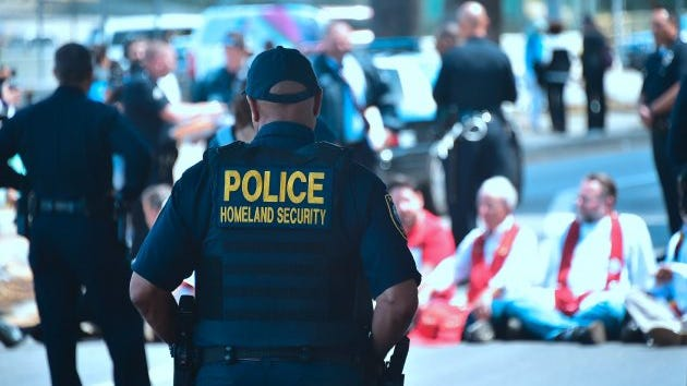 A Department of Homeland Security officer watches as police arrest demonstrators protesting recent enforcement actions by Immigration and Customs Enforcement (ICE) outside the ICE headquarters in downtown Los Angeles on April 13, 2017.