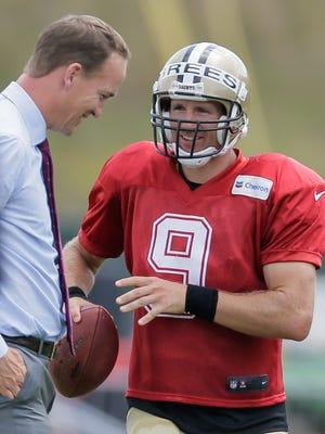 New Orleans Saints quarterback Drew Brees (9) talks with retired NFL quarterback Peyton Manning during NFL football training camp in White Sulphur Springs, W.Va., Sunday, July 31, 2016.