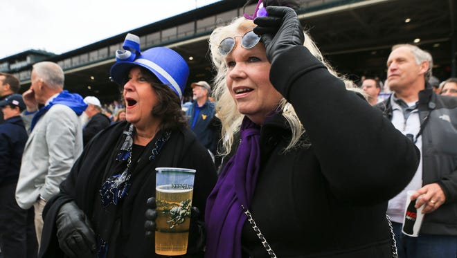Elspeth Cobb, right, had to left her sunglasses to check out the race results while at Keeneland with friend Rita Klinger, left, after the first race Friday.