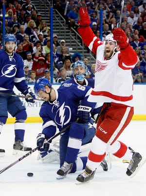 Detroit Red Wings center Landon Ferraro, right, celebrates a Detroit goal as Tampa Bay Lightning's Anton Stralman (6), goalie Ben Bishop (30) and Victor Hedman (77) react during the second period in Game 5 of a first-round NHL hockey playoff series, Saturday, April 25, 2015, in Tampa, Fla.