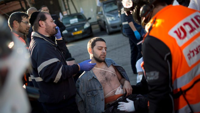 An injured man is treated by paramedics at the scene of a stabbing in Tel Aviv, Israel, Wednesday, Jan. 21, 2015.