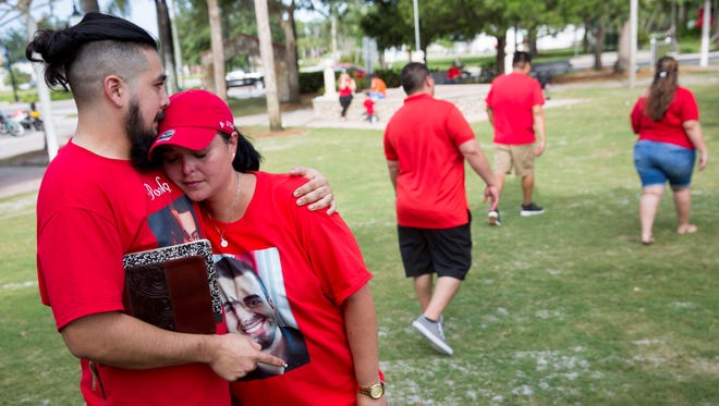"Johnathan Valero, a cousin of Jordan Valero, comforts Becky Calzadilla, mother of Jordan Valero, at Riverside Park on Sunday, July 9, 2017, in Bonita Springs. ""It's humbling,"" Calzadilla said in response to the turnout. ""Jordan was very much loved. We're not giving up."" Proceeds from the event will go toward a reward for any information leading to the arrest of a suspect."