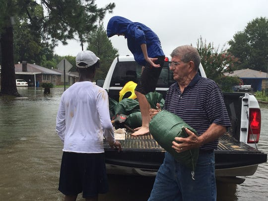 Roland Hines and his children help their Knollwood Drive neighbors sandbag their homes Saturday in Lafayette.