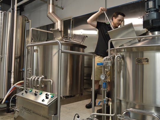 Andrew Harton stirs a batch of beer at Big Oyster Brewery
