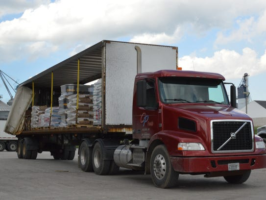 A delivery truck is loaded with animal feed at the