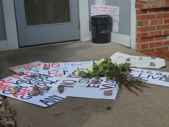 Marchers left white roses and signs outside U.S. Rep.