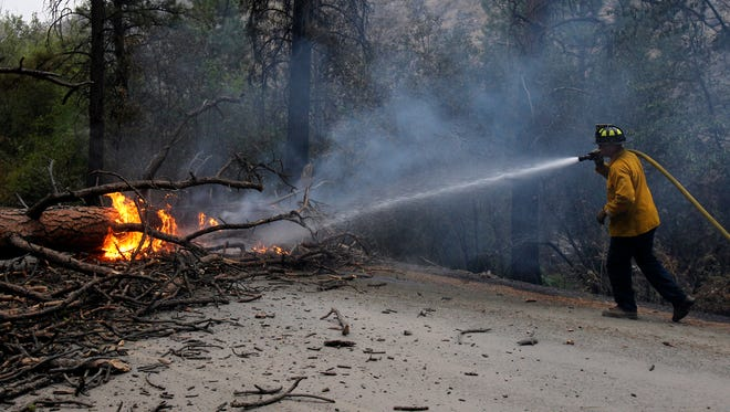 Firefighter Ryan Sundberg puts out a burning tree which fell across Salmon Creek Road outside of Okanogan County, as wildfires continue to burn throughout Washington, in Omak, Wash., on Aug. 21, 2015.