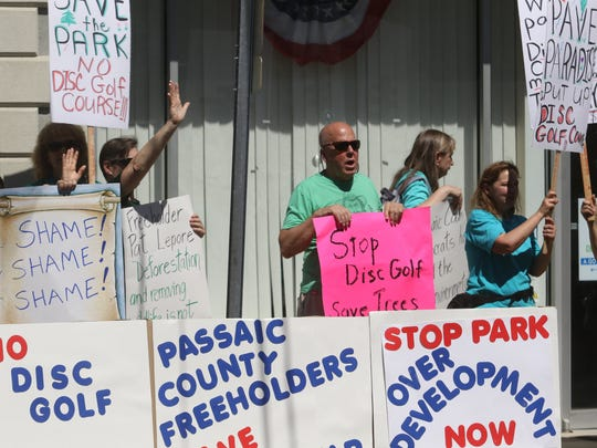 A group of concerned citizens protested against changes at Rifle Camp Park where a disc golf course and other development is proposed. They are protesting the decision made by the Passaic County Board of Freeholders in front of the Passaic County Democratic Party Committee headquarters.