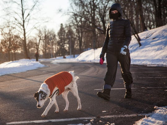 Sarah Enloe walks her dog Alle around the loop at Gypsy Hill Park, both bundled up against the frigid single-digit temperatures, on Thursday, Feb. 19, 2015.
