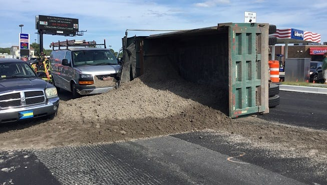 Dirt covers the Atlantic Avenue where a Mack dump truck tipped after apparently taking the turn from Roxana Road too fast, according to the Delaware State Patrol. The dump truck driver was cited for careless driving.