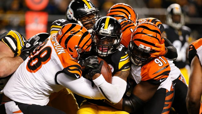 The Cincinnati Bengals defensive tackle Brandon Thompson (98) and the defensive end Robert Geathers (91) fight to tackle the Pittsburgh Steelers running back Le'Veon Bell (26) at Heinz Field.