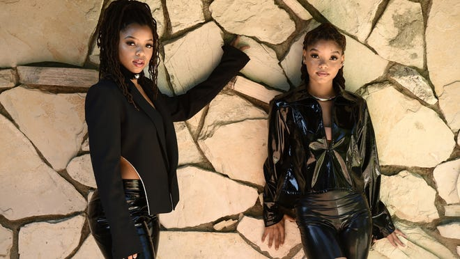 """Chloe Bailey, left, and her sister Halle Bailey, of the R&B duo Chloe X Halle, pose for a portrait in their backyard in Los Angeles to promote their latest release, """"Ungodly Hour."""""""