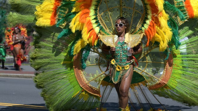 Tamara Shillingford hydrates in her colorful costume along the Caribbean Carnival parade route.