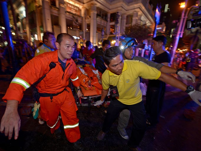 Thai rescue workers carry an injured person after a