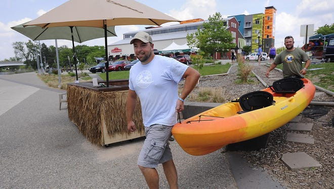 Paul Brogan, left, and Nate Williams, right, haul a kayak into place at their River Town Adventures stand near Lansing's City Market.