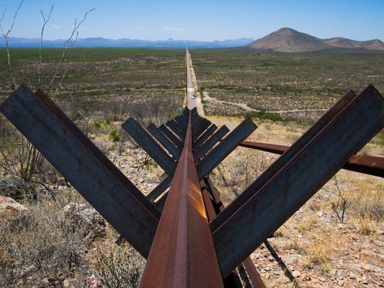 A vehicle barrier with Mexico (left) ends at a hill in Douglas, Arizona, about six miles from the state line with New Mexico.