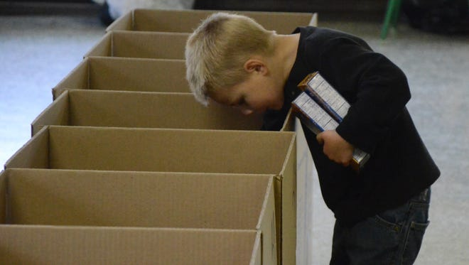 Christian Moore, 4, checks one of the boxes before adding macaroni and cheese.