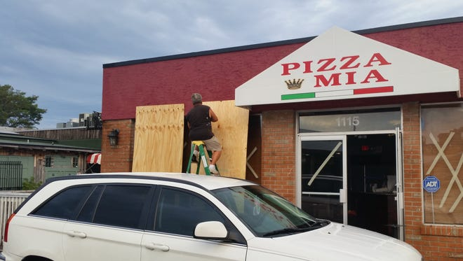 7:50 a.m. Peter Schaepe , owner of Pizza Mia on U.S.1 and 10th Avenue in Vero Beach installing plywood.