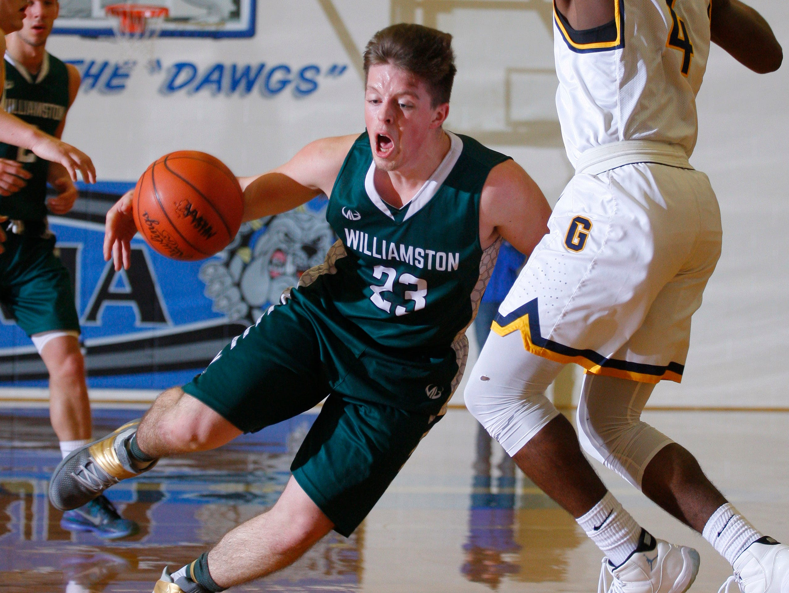 Williamston's Cole Kleiver, left, dribbles past pressure form Godwin Heights' Suriya Davenport during their MHSAA regional game Monday, March 13, 2017, in Ionia, Mich. Williamston won 69-65..