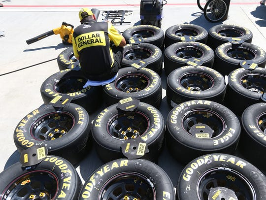 A crew member prepares tires on pit road prior to last